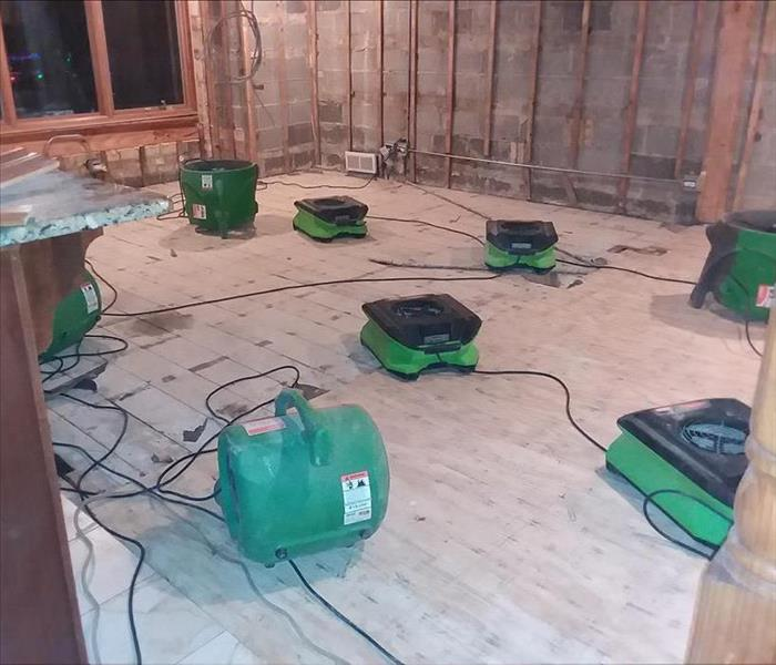 This is the same room that the drywall and the floor has been removed. Air movers are drying the materials.