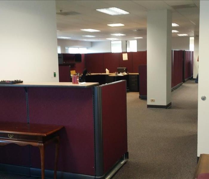This is a photo of an office, with a desk in the foreground and cubicles in the background.