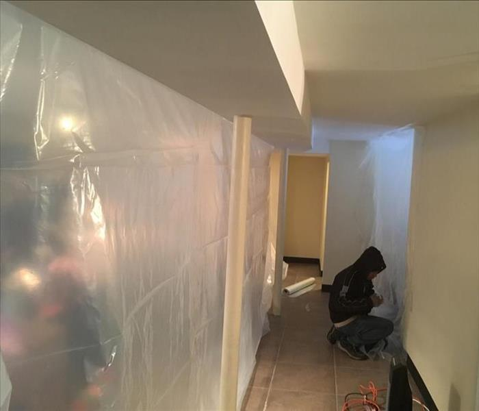 male kneeling down working on drywall