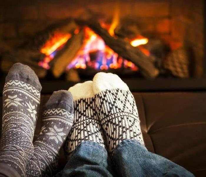two pairs of feet in socks relaxing in front of a fireplace.